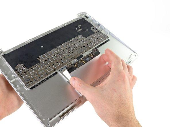 Hebe die Kante des Trackpads nahe der Tastatur vorsichtig mit dem flachen Ende des Spudgers aus ihrer Vertiefung im oberen Gehäuse, indem du sie aus den Halterungen, die am oberen Gehäuse angebracht sind, weghebst.