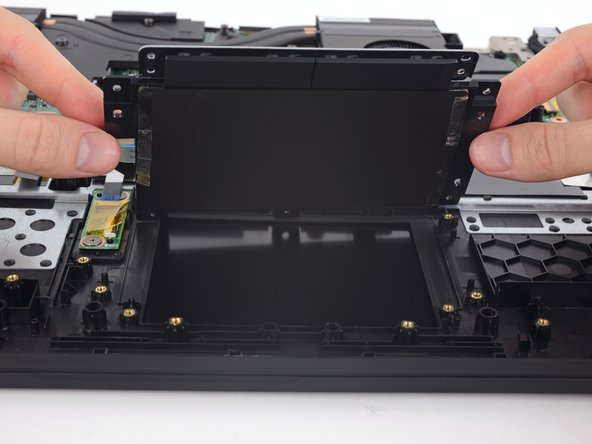 Seven Phillips screws secure the trackpad and button assembly.