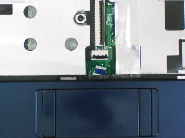 Using the blue tab, pull the trackpad ribbon cable from its socket on the motherboard.