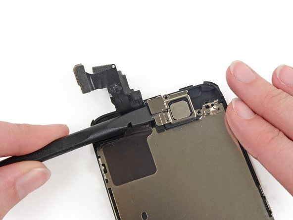 Use the flat edge of a spudger to push the earpiece speaker bracket off the display assembly.