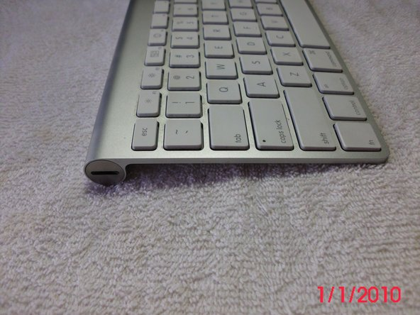 To open the battery compartment, on the left side of the keyboard use a coin to loosen the screw off cover.