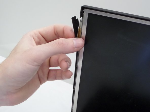 Using your index finger and thumb, gently lift and pull away laptop closure latch of the side of the screen assembly.