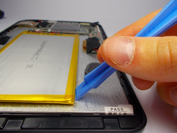Using a plastic opening tool, gently pry the edges battery off of the backside of the touchscreen display. Start at the end of the battery opposite the connecting wires.