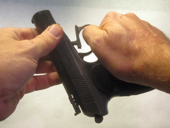 While maintaining a firm grip on the slide, pull downward on the trigger guard, unlocking the slide from the frame.