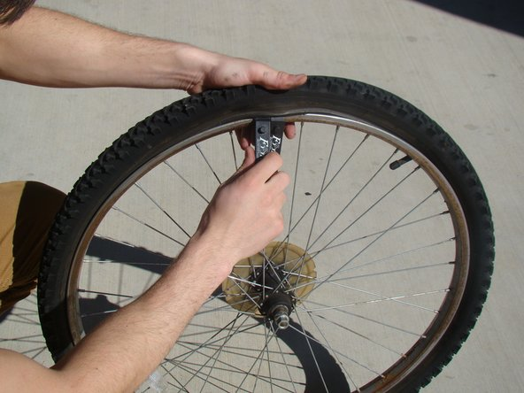 Insert the second tire lever next to first and slowly slide it along the outside edge of the rim until one side of the tire is off the rim.