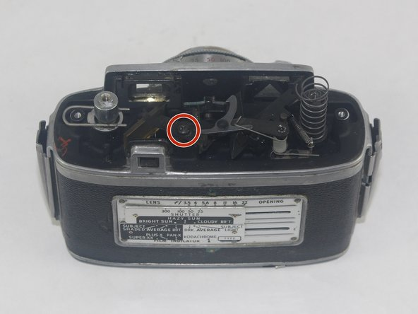 Image 1/2: With the 2.5mm flathead screwdriver, loosen the horizontal-facing 2.1mm flathead screw that holds the metal bracket in place and set it aside.