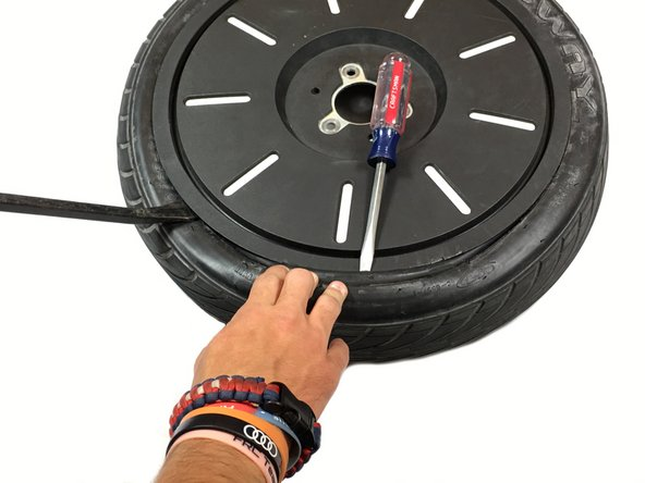 Using the flathead screwdriver, wedge it between the rubber and the rim to prevent the tire from returning to its original position.