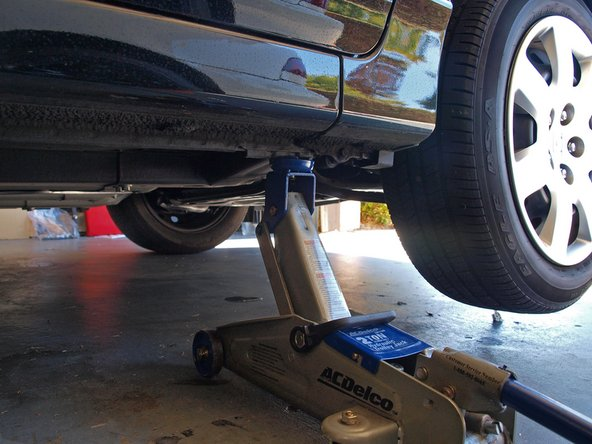 Use the jack to lift the passenger side of the car until you have enough room to work under the car comfortably.