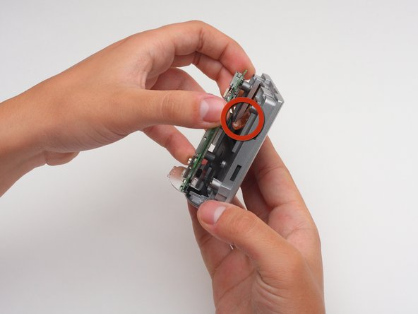 Image 1/2: To do so, you must use the back end of the spudger to push out the two white tabs connected to the wire, that holds the motherboard and front cover together.