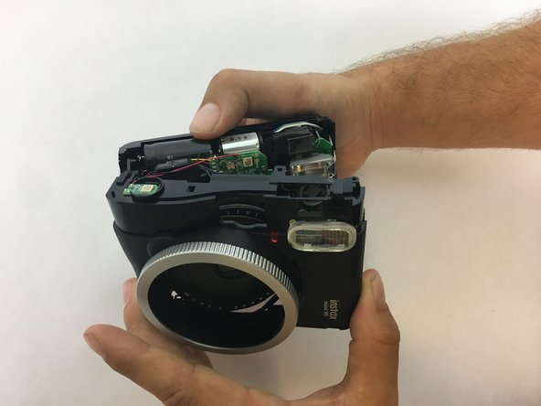 Open up the camera by releasing the latches on the top and bottom of the camera. There are 2 latches on top and 2 on the bottom. Once the two halves of the camera are unhooked, you can easily pry open the camera with your hands.