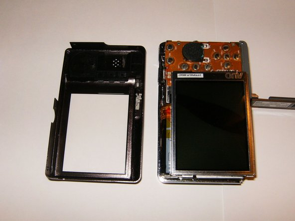 The rear cover can now be easily removed. The LCD is sitting in a frame without fasteners. It will just lift up, however, there will be a piece of insulating material that is separating the back of the LCD from the logic board. Remove this after the removal of the LCD from the frame. Do not try to remove the LCD from the PCB yet.