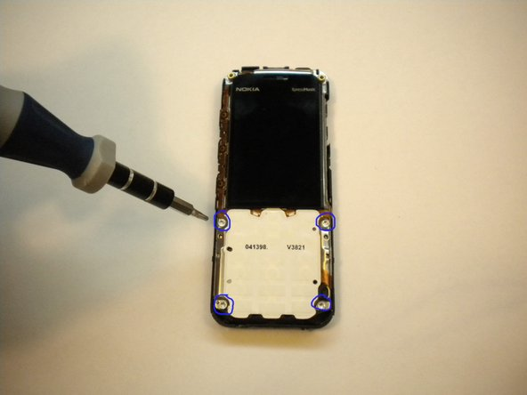 Flip over the phone and again us the T6 torx head to remove the 4 screws located at each corner of the white keypad base