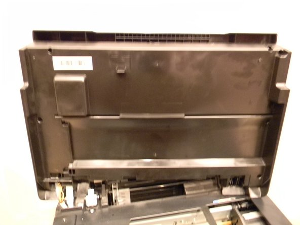 With the printer facing away from you, lift up on the right hand side of the lid of the printer and slide it to the left to remove it.