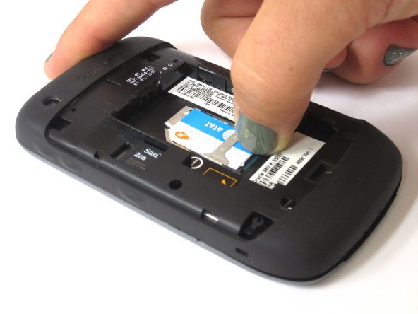 Place thumb on bottom of SIM card.  Apply light pressure and slide SIM card up.
