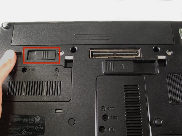 Flip the laptop over and locate the battery compartment release latch.