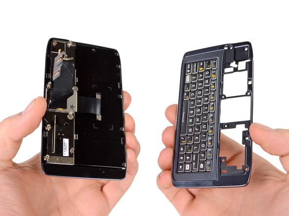 Image 2/2: In order to complete this feat we have to remove some Torx screws and separate the keyboard top from the rest of the phone.