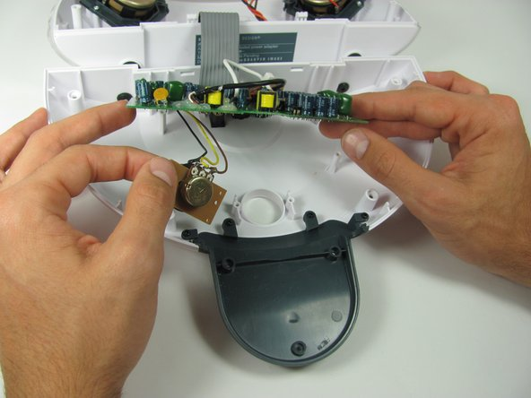 Image 1/3: Turn over the motherboard and remove the solder connecting the wide, flat, grey wire.
