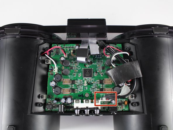 Image 1/3: Unplug the wide red/white/black wire bundle from the lower right-hand corner of the motherboard by pulling it out of their connection.
