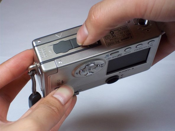 On the bottom of the camera, use your thumb to press the rubber battery cover towards the side of the camera with the strap base. The cover will shift to extend beyond the rest of the camera.