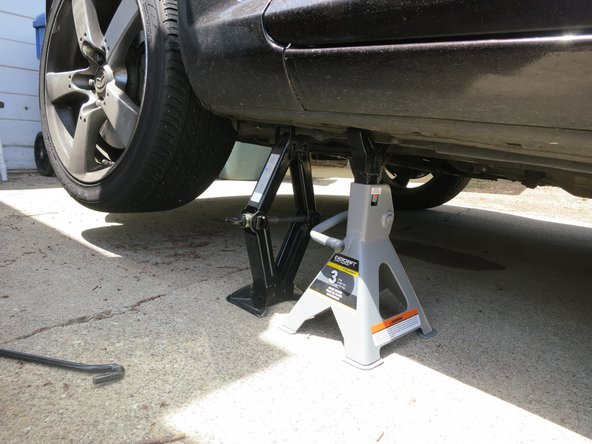 Put the jack stand under the car to ensure the car will not fall back down while you are working on it.