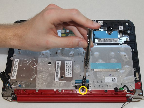 Image 2/2: Remove the 3mm screw under the keyboard cable using the PH0 screwdriver.