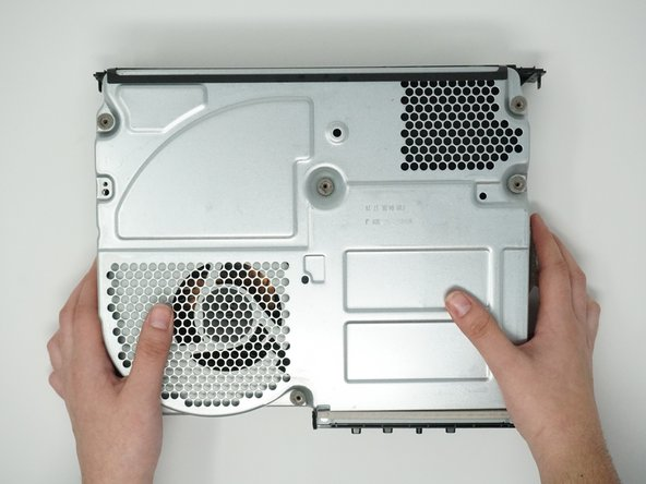 Remove the metal casing by pulling it upward, revealing the interior components of the device.