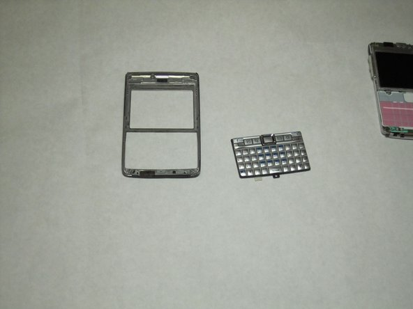 Once the front cover has been removed, there is nothing holding the keyboard to the rest of the phone. Simply remove the keyboard from the cover by lifting the keyboard from its interior side.