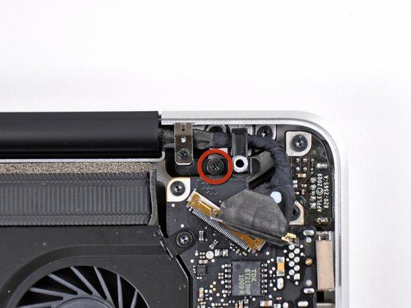 Dévissez la vis cruciforme de 8,6 mm fixant le support du câble de données de l'écran au boîtier supérieur.
