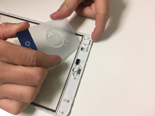 Use the plastic card to separate the glass from the front panel.