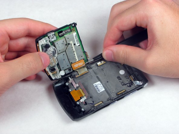 Using tweezers, disconnect the copper ribbon on the left side of the phone by pulling it up from the circuit board.