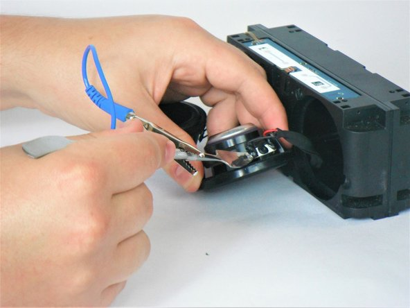 Using the anti-static wrist strap and the metal spudger, remove the wires from the speakers.