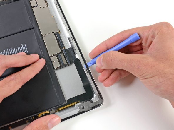 Image 3/3: Carefully slide the plastic opening tool along the edge of the iPad, releasing the adhesive.
