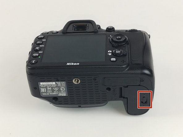 Open the battery compartment on the bottom of the camera by sliding the release button.