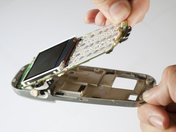 Gently remove the logic board and LCD screen from the back cover of the phone.