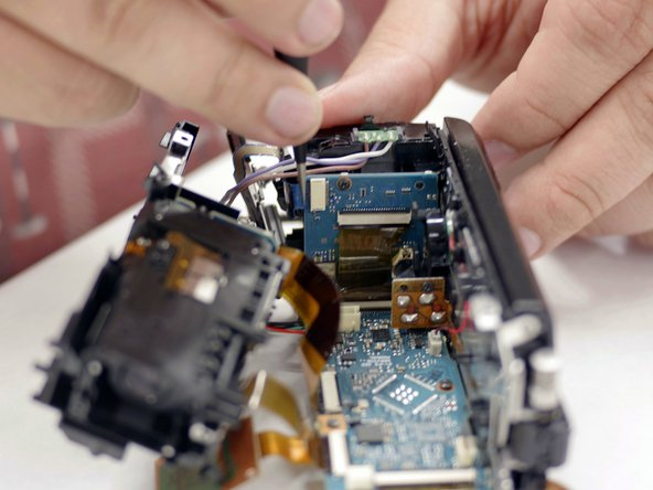Orienting the camera such that the front side is facing you, remove the ribbon connecting the start and zoom buttons to the powerboard using your tweezers.
