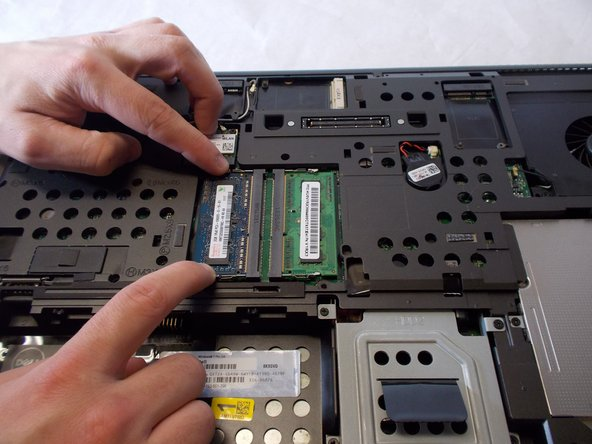 The RAM is held in place by two prongs. By pulling the two prongs lightly away from the chip the RAM is able to be pulled out.