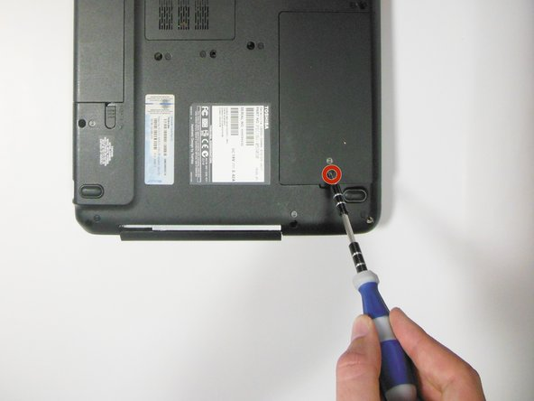"""Unscrew the 5.5 mm """"F5"""" screw using the Phillips #0 screwdriver, and carefully remove the plastic cover."""