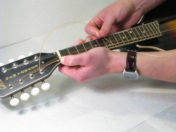 Pull the string down, towards the fretboard, and run the string underneath itself.