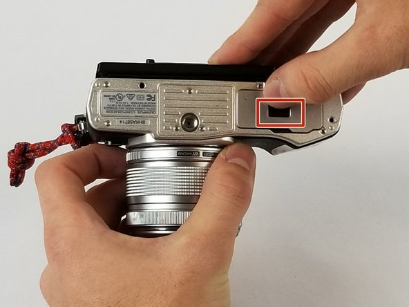 Open battery/SD card door latch by moving the black button in the direction of the arrow, towards the camera screen.