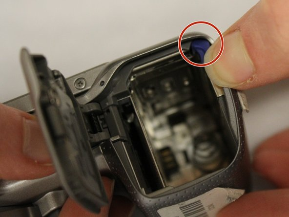 Press the lock lever to the left. This will eject the camera battery.