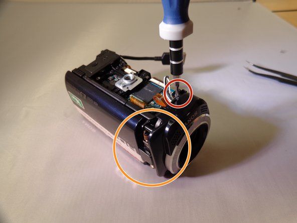 The silver screw is located on the front right of the camera, and is attached to the main panel of the camera.