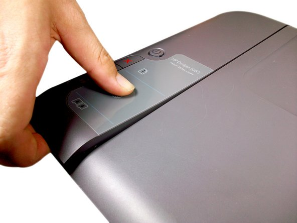 Press your thumb down on the center of the button plate located on the left side of the printer.