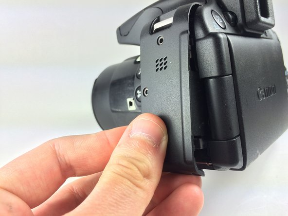 Use the plastic opening tool to carefully start lifting up the camera's left-side panel. Then use your fingers to pry off the rest.
