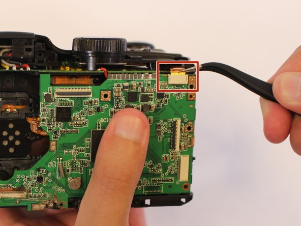 Using the tweezers, disconnect the orange cable connection at the top of the motherboard near the mode dial.
