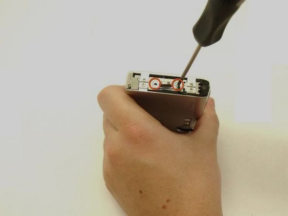On the right hand side of the camera, remove the two screws from the wrist strap handle by using the Phillips screwdriver.