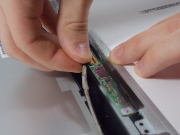Hold the tape back with one hand and pull the connector out