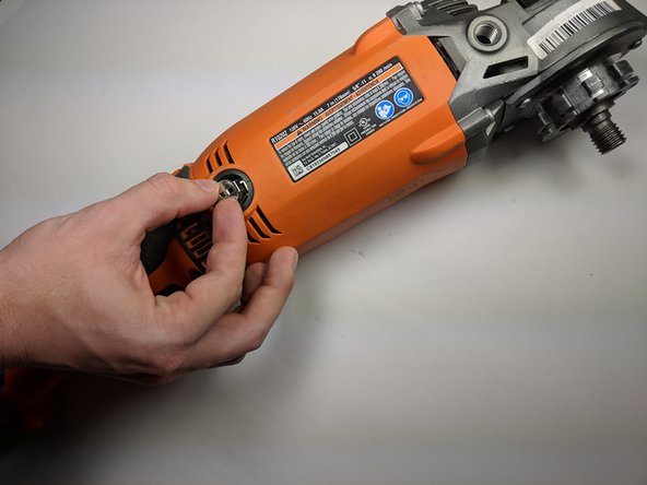 Using your fingers, gently lift the carbon brush up and out of its housing.