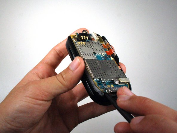 Image 1/2: Use the spudger to lift the motherboard out of the base of the phone.