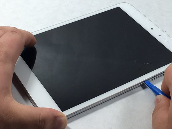 Image 1/2: Use a plastic opening tool to remove the metal backing of the tablet.