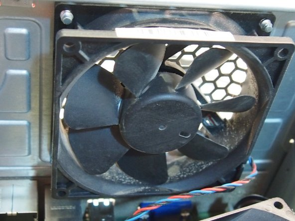 The fan is held on by four screws that you must unscrew from the outside of the computer.